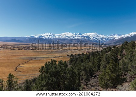 Alpine meadow with Sierra Nevada mountains covered by snow - stock photo