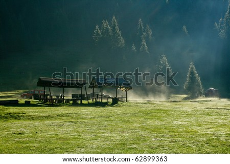 Alpine plateau with camping site and morning dew - stock photo