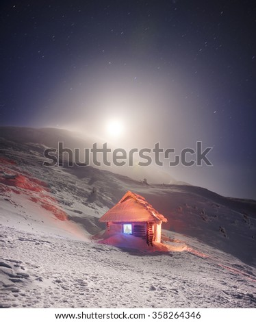 Alpine refuge for those who are celebrating the ascent to the highest peak of Ukraine - Goverla on the background of the Montenegrin ridge. Hurricanes sweep it snow, but it still helps climbers - stock photo