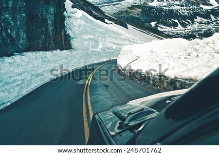 Alpine Road Drive During Spring. Dangerous Snow Piles on Sides of the Mountain Road. High Mountains Road Trip. - stock photo