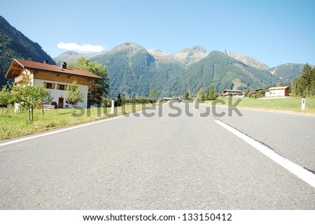 Alpine road leading to mountains in Austria - stock photo