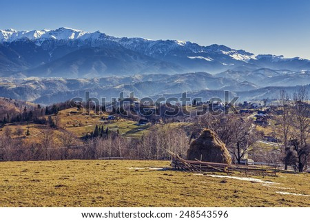 Alpine rural scenery with small sheep pen, haystack and remote village in the valleys of Bucegi mountains, Brasov county, Romania. - stock photo