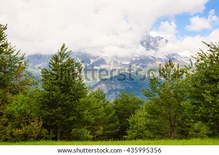 Alpine scenery. A view from pasture through the woods on the peaks of Alps mountains covered with snow in Provence-Alpes-Cote d'Azur region of France. - stock photo