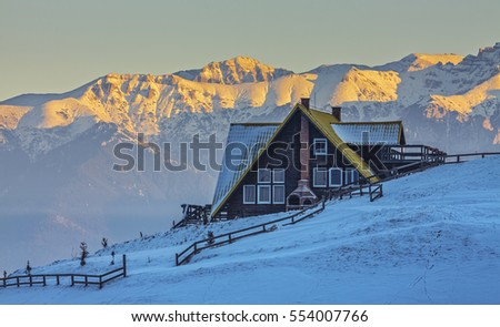 Alpine scenery with rustic wooden cottage and yellow snow capped ridge of the Bucegi mountains in the sunrise light on a cold serene winter morning, in the Bran-Rucar pass, Transylvania, Romania.