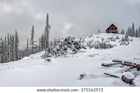 Alpine Snow Hut Offers Shelter just Across Open Snow Field in Winter Mountain Scene - stock photo