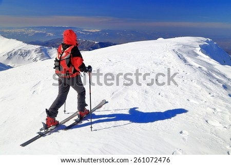 Alpine tourer ascending on skies in sunny day of winter - stock photo