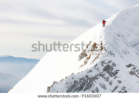 Alpinist descending an icy slope - stock photo