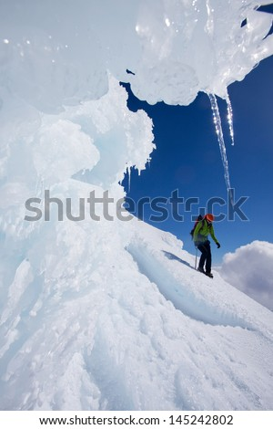Alpinist descending snow covered mountain slope - stock photo