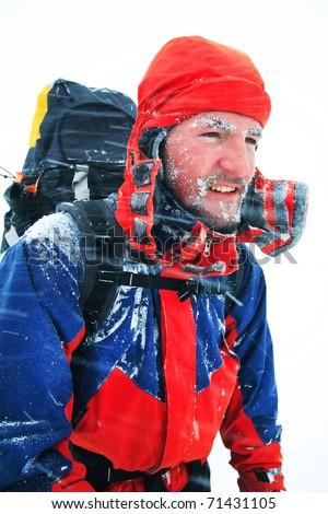 Alpinist facing a winter blizzard - stock photo