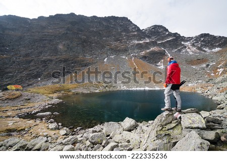 Alpinist on the shore of an alpine lake - stock photo