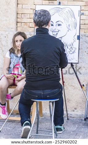 Altea, Alicante, Spain - April, 20, 2014: An artist draws the cartoon of a girl in the tourist zone of Altea in Spain - stock photo