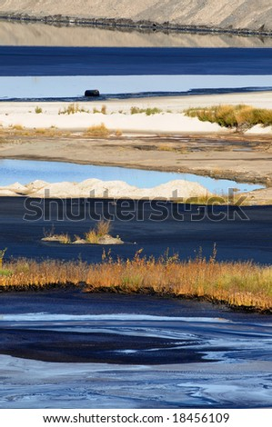 Alternating stripes of bitumen, water, sand and grass at a mine's tailings pond, where fine waste gradually settles. Also one oil barrel visible. - stock photo