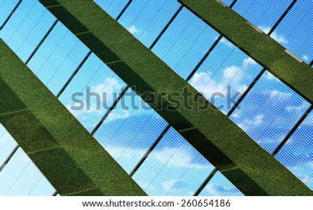 Alternative Energy Concept. Top View of Modern Solar Panels Farm on beautiful Green Grass with Reflecting Sunshine and Clouds - stock photo