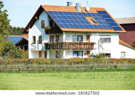 Alternative energy. Solar panels on modern house cottage roof - stock photo