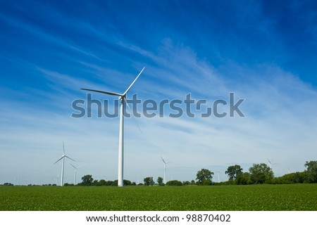 Alternative energy wind power generator turbine in corn field with blue sky - stock photo