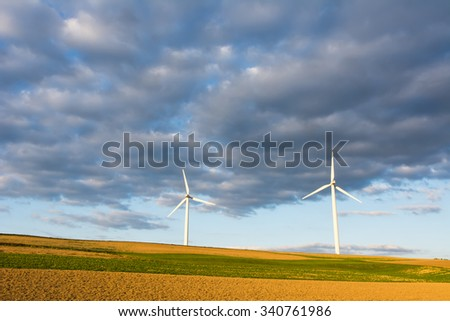 Alternative energy with wind power - three windmill silhouettes in the sunset. - stock photo