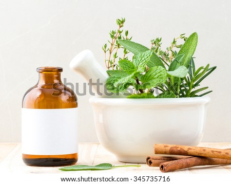 Alternative health care fresh herbal and  Bottle of aromatherapy in mortar on wooden background. - stock photo