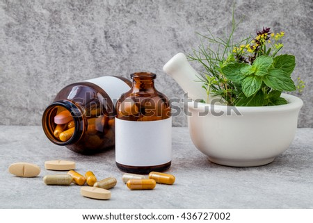 Alternative health care fresh herbs  rosemary ,lemon thyme ,fennel ,peppermint ,basil flower and herbal capsule with mortar on stone background. - stock photo