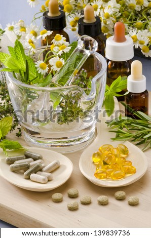 Alternative Medicine. Rosemary, mint, chamomile, thyme in a glass mortar. Essential oils and herbal supplements. - stock photo