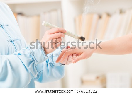 Alternative medicine therapist doing moxa treatment on her client - stock photo