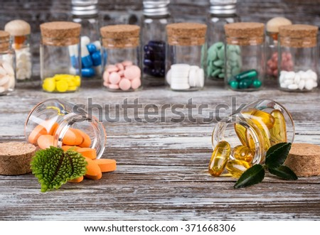 Alternative medicines with green leaves in glass containers in front versus traditional medicine in the back - stock photo