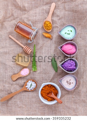Alternative skin care and homemade scrubs with natural ingredients sage ,turmeric ,sea salt ,honey, aloe vera,lemon ,rosemary,mint and sesame on brown cloth sack  background. - stock photo