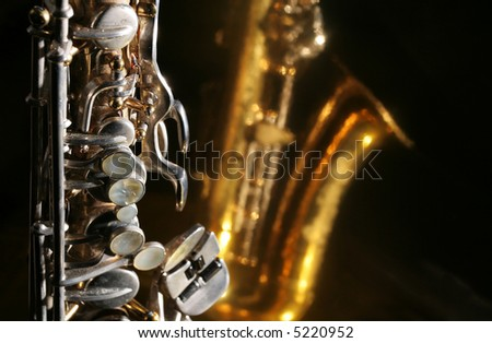 Alto saxophone keys against a dark reflective background with copy space