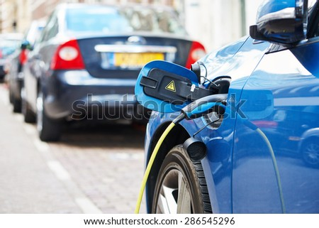 Altrernative eco energy fuel. Close up of the power supply plugged into an electric car during charging in Amsterdam - stock photo