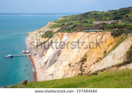 Alum Bay Isle of Wight beautiful beach and colourful rocks next to the Needles tourist attraction - stock photo