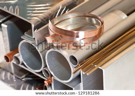 Aluminium, copper pipe and profile, bronze bars - stock photo