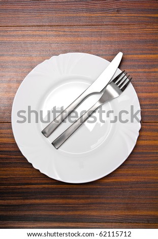 Aluminium fork and knife on a white plate - stock photo