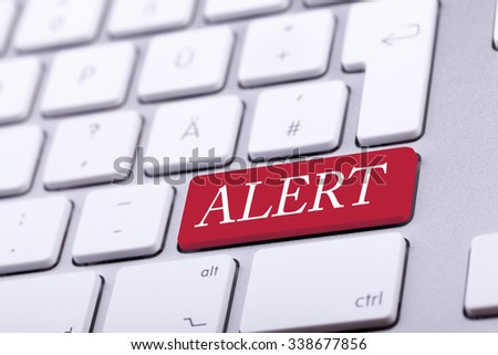 Aluminium keyboard with alert word on it on red key. Danger and alert - stock photo