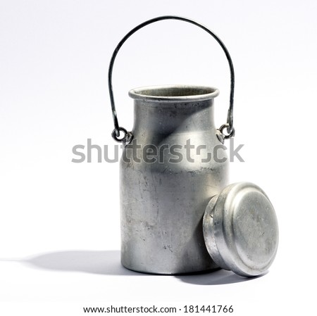 Aluminium milk bottle or urn with the handle raised and the lid propped up against it on the side, over a white background with copy space