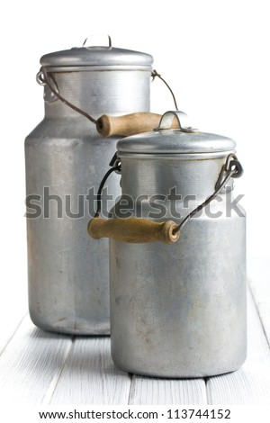 aluminium milk can on wooden table - stock photo