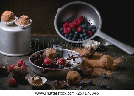 Aluminium plate with chocolate mixture for making chocolate truffles and homemade chocolate truffles with fresh berries over dark table. - stock photo