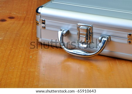 Aluminum brief case on old vintage table - stock photo
