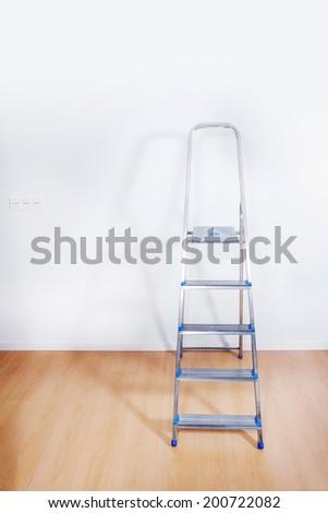 Aluminum ladder in interior room - stock photo