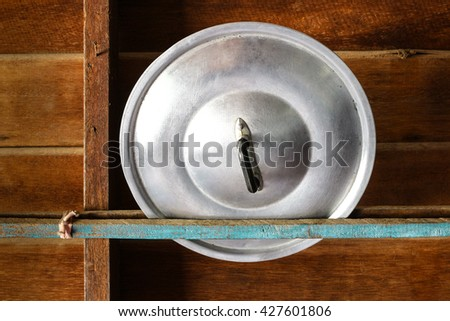 Aluminum lid on the old wooden floor. - stock photo