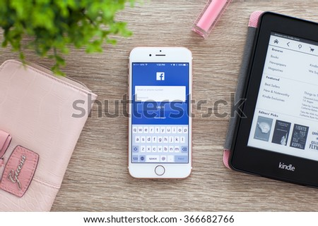 Alushta, Russia - November 5, 2015: iPhone 6S Rose Gold with social networking service Facebook on the screen in the table. iPhone 6S was created and developed by the Apple inc. - stock photo