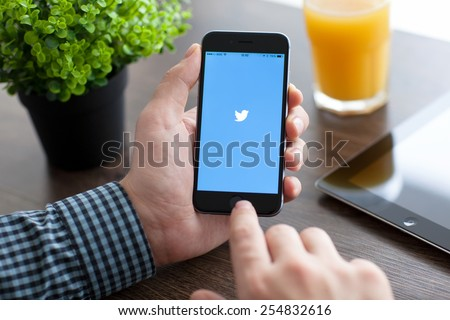 Alushta, Russia - November 21, 2014: Man holding a iPhone 6 Space Gray with social networking service Twitter on the screen. iPhone 6 was created and developed by the Apple inc. - stock photo