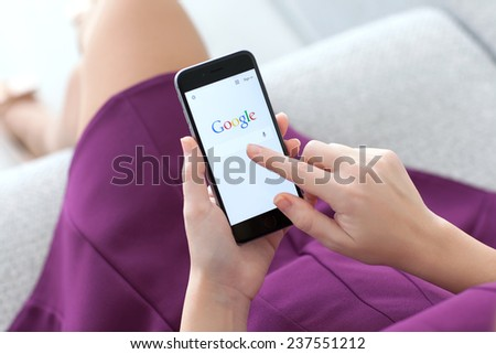 Alushta, Russia - November 22, 2014: Woman holding a iPhone 6 Space Gray with social networking service Google on the screen. iPhone 6 was created and developed by the Apple inc. - stock photo