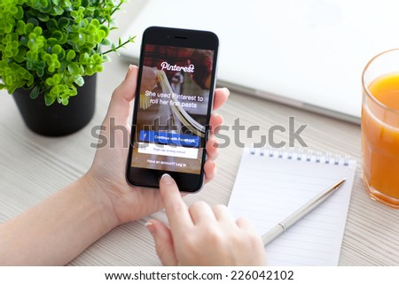 Alushta, Russia - October 24, 2014: Girl holding a iPhone 6 Space Gray with social Internet service Pinterest on the screen. iPhone 6 was created and developed by the Apple inc. - stock photo