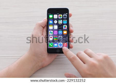 Alushta, Russia - October 23, 2014: man holding new phone iPhone 6 Space Gray over the table. iPhone 6 was created and developed by the Apple inc. - stock photo