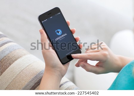 Alushta, Russia - October 29, 2014: Woman holding a iPhone 6 Space Gray with social networking service LiveJournal on the screen. iPhone 6 was created and developed by the Apple inc. - stock photo
