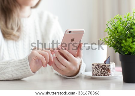 Alushta, Russia - October 25, 2015: Woman holding in the hand iPhone 6 S Rose Gold in cafe. iPhone 6S was created and developed by the Apple inc. - stock photo