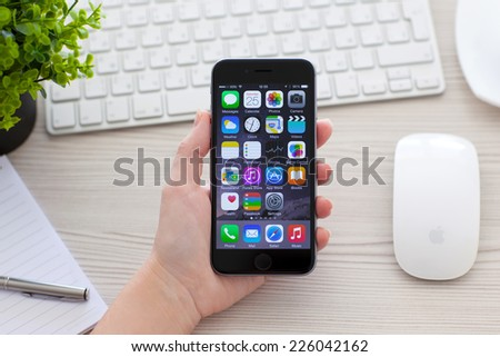 Alushta, Russia - October 25, 2014: Woman holding new phone iPhone 6 Space Gray over the table. iPhone 6 was created and developed by the Apple inc. - stock photo