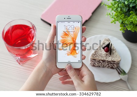 Alushta, Russia - October 25, 2015: Woman unlock phone iPhone6S Rose Gold over the table. iPhone 6S Rose Gold was created and developed by the Apple inc. - stock photo