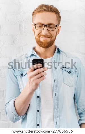 Always connected. Happy young bearded man holding mobile phone and smiling while standing against brick wall - stock photo