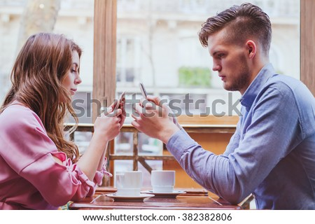 always connected, internet addiction, young couple in cafe looking at their smartphones, social network concept - stock photo