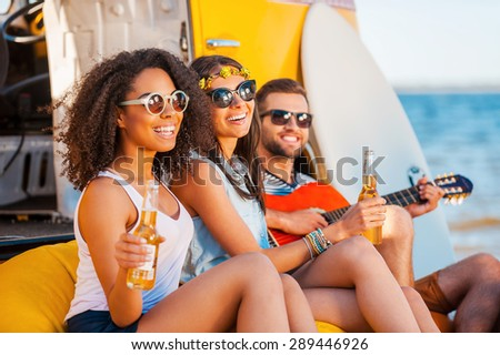 Always happy together. Three cheerful young people drinking beer and playing guitar while sitting on the beach near retro van - stock photo